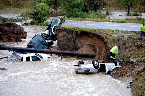 "A bridge collapse after flash flooding on a business access road at Highway 287 and Dillon Road at the Broomfield/Lafayette border, Colo., causes 3 cars to fall in the creek on Thursday, Sept. 12, 2013. The National Weather Service has warned of an ""extremely dangerous and life-threatening situation"" throughout the region. (AP Photo/Daily Camera, Cliff Grassmick) NO SALES NO MAGS; NO TV;"