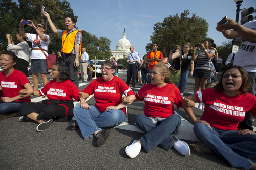 Women link arms and sit in a circle to block the intersection of Independence Avenue SE and New Jersey Avenue SE outside the House of Representatives on Capitol Hill in Washington, Thursday, Sept. 12, 2013, to protest Congress' inaction on comprehensive and inclusive immigration reform. They are all arrested soon after this images is taken. (AP Photo/Carolyn Kaster)