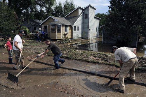 Brian Guse, center, and Matt Bruce, right, clear mud and debris from the street that was flooded in Longmont, Colo., on Saturday, Sept. 14, 2013. Floodwaters have affected a 4,500 square-mile section of the state. National Guard helicopters have been evacuating residents from the hardest hit communities. (AP Photo/Chris Schneider)