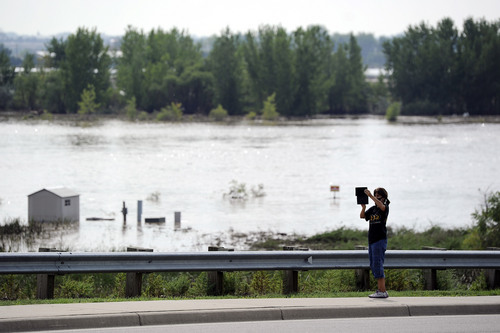 Stefanie Coltrain, 46, takes a picture of the St. Vrain River which has over flown its banks near Longmont, Colo., on Saturday, Sept. 14, 2013. Floodwaters have affected a 4,500 square-mile section of the state. National Guard helicopters have been evacuating residents from the hardest hit communities. (AP Photo/Chris Schneider)