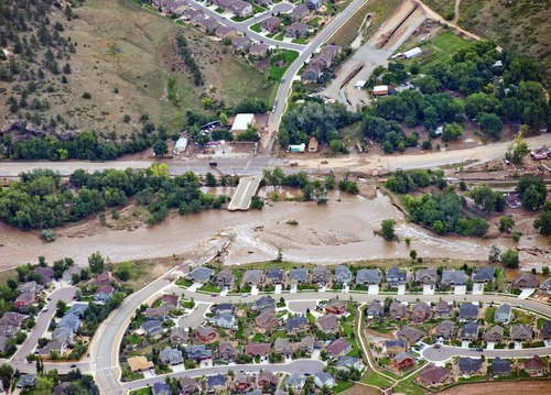 A residential neighborhood and a connecting road in Lyons, Colo., are cut in two by flood waters as flooding continues to devastate the Front Range and thousands are forced to evacuate with an unconfirmed number of structures destroyed Friday, Sept. 13, 2013. (AP Photo/John Wark)