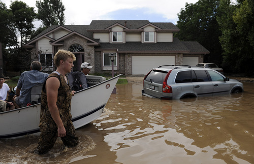 Chris Schneider  |  The Associated Press Eric Machmuller, front left, and Pat Machmuller, rear left, lead a boat down a residential street to help residents gather pets and belongings from their flooded homes in Longmont, Colo., on Saturday. Floodwaters have affected a 4,500 square-mile section of the state. National Guard helicopters have been evacuating residents from the hardest hit communities.