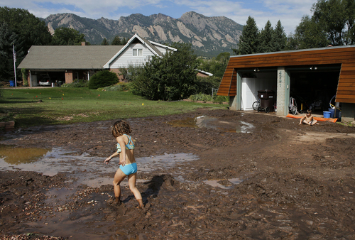 Noe Sura, 7, left, and her brother Eli, 7, play in the mud clogged yard around their home after days of flooding, on the southern edge of Boulder, Colo., Saturday Sept. 14, 2013. By air and by land, the rescue of hundreds of Coloradoans stranded by epic mountain flooding was accelerating as food and water supplies ran low, while thousands more were driven from their homes on the plains as debris-filled rivers became muddy seas inundating towns and farms miles from the Rockies. (AP Photo/Brennan Linsley)