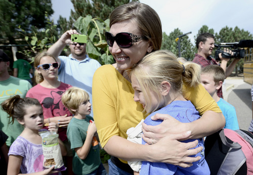 Bonnie Dannelly  hugs her daughter Makayla after she got off the bus at Fireside Elementary in Louisville, Colo., Saturday Sept. 14, 2013. Makayla Dannelly was one of over 80 Fireside 5th graders who were trapped above Jamestown at Camp Cal-Wood.   (AP Photo/Daily Camera, Mark Leffingwell)