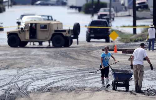 Residents clear mud and debris from the street that was flooded in Longmont, Colo., on Saturday, Sept. 14, 2013. Floodwaters have affected a 4,500 square-mile section of the state. National Guard helicopters have been evacuating residents from the hardest hit communities. (AP Photo/Chris Schneider)