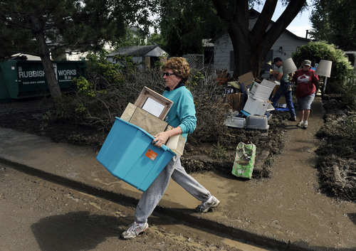 Lonnie Dooley helps a neighbor clear belongings from their home which was flooded in Longmont, Colo., on Saturday, Sept. 14, 2013. Floodwaters have affected a 4,500 square-mile section of the state. National Guard helicopters have been evacuating residents from the hardest hit communities. (AP Photo/Chris Schneider)