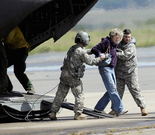 A woman is  helped off of a military helicopter at the Boulder Municipal Airport in Boulder, Colo., on on Monday,  Sept. 16,  2013, after being rescued. Thousands of people remained stranded by high water and washed out roads in the state. (AP Photo/Ed Andrieski)