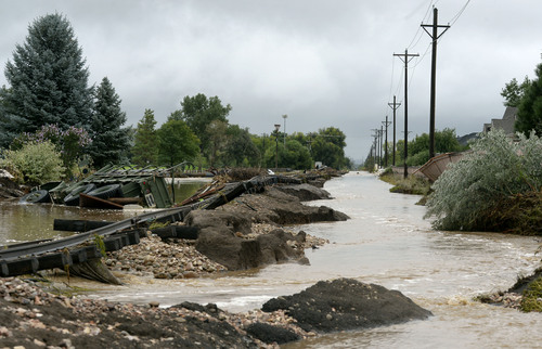 A truck rests next to the washed out railroad track in the Champion Greens neighborhood in Longmont,  Colo., Sunday Sept. 15, 2013.  Evacuations are underway Sunday morning in some Longmont neighborhoods because the St. Vrain River is rising quickly. (AP Photo/ The Denver Post, Craig F. Walker)