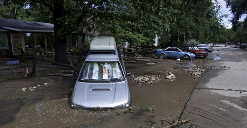 ADDS MAGS OUT-This photo taken on Friday, Sept. 13, 2013, shows vehicles damages by flood waters on a street in Lyons, Colo.  Access to the small mountain town was cut off after bridges were destroyed by flash flooding. Days of rain and floods have transformed the outdoorsy mountain communities in Colorado's Rocky Mountain foothills from a paradise for backpackers and nature lovers into a disaster area with little in the way of supplies or services. Roadways have crumbled, scenic bridges are destroyed, and most shops are closed.(AP Photo/Kenneth Wajda)