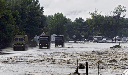 ADDS MAGS OUT-This photo taken on Friday, Sept. 13, 2013, shows National Guard trucks making their way down one of the main streets in Lyons, Colo.  Access to the small mountain town was cut off after bridges were destroyed by flash flooding. Days of rain and floods have transformed the outdoorsy mountain communities in Colorado's Rocky Mountain foothills from a paradise for backpackers and nature lovers into a disaster area with little in the way of supplies or services. Roadways have crumbled, scenic bridges are destroyed, and most shops are closed.(AP Photo/Kenneth Wajda)