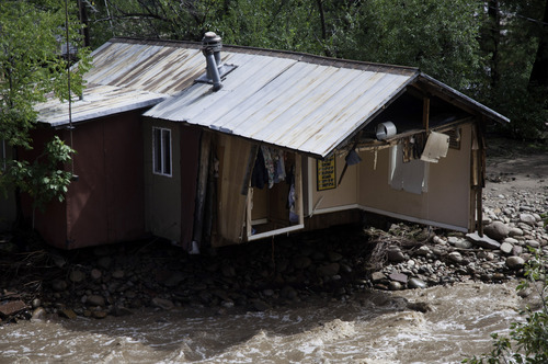 ADDS MAGS OUT-This photo taken on Friday, Sept. 13, 2013, shows the foundation of a house being undercut  in Lyons, Colo.  Access to the small mountain town was cut off after bridges were destroyed by flash flooding. Days of rain and floods have transformed the outdoorsy mountain communities in Colorado's Rocky Mountain foothills from a paradise for backpackers and nature lovers into a disaster area with little in the way of supplies or services. Roadways have crumbled, scenic bridges are destroyed, and most shops are closed.(AP Photo/Kenneth Wajda)