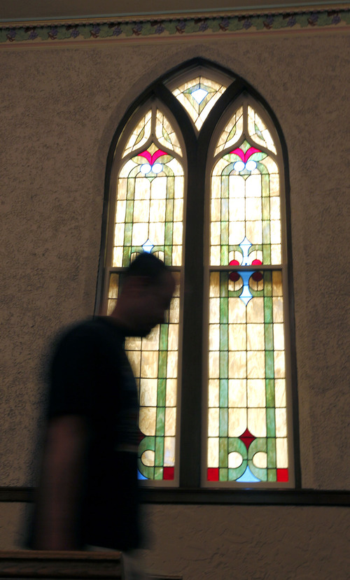 Al Hartmann     The Salt Lake Tribune A worker passes beneath a stained glass window in the restored chapel of an old LDS Church at 2115 Jefferson Ave. in Ogden that is nearing completion. It first opened in 1937.