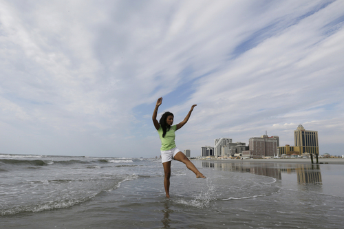Miss America 2014 Nina Davuluri kicks water during the traditional dipping of the toes in the Atlantic Ocean the morning after being crowned Miss America, Monday, Sept. 16, 2013, in Atlantic City, N.J. Davuluri represented New York.  (AP Photo/Julio Cortez)
