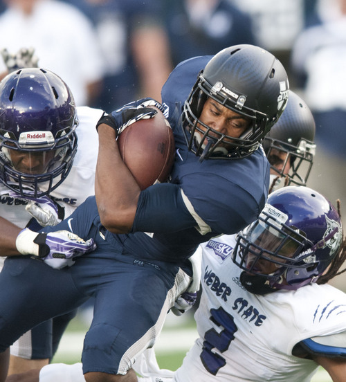 Utah State's Joe Hill is tackled by Weber State defense in the second quarter of the game at Romney Stadium in Logan, Utah Saturday.