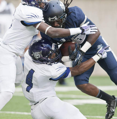 Utah State's Ronald Butler is tackled by Weber State's Robbie Diamond (far left) and Chris Jones in the game at Romney Stadim Saturday. (Jennifer Meyers/Herald Journal)
