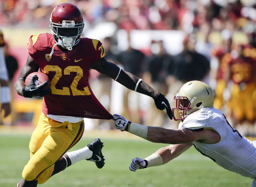 Southern California running back Justin Davis, left, scores after breaking away form Boston College defensive back Sean Sylvia during the second half of an NCAA college football game in Los Angeles, Saturday, Sept. 14, 2013. USC won 35-7. (AP Photo/Chris Carlson)