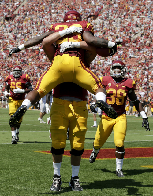 Southern California running back Tre Madden, top, celebrates with offensive tackle Kevin Grafafter after Madden scored against Boston College during the first half of an NCAA college football game in Los Angeles, Saturday, Sept. 14, 2013. (AP Photo/Chris Carlson)