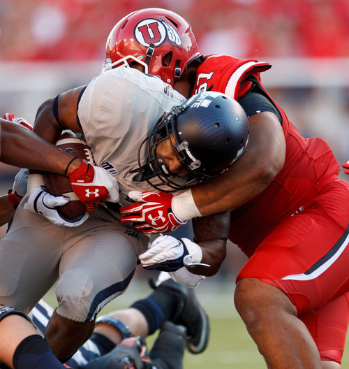 Trent Nelson  |  The Salt Lake Tribune Utah State Aggies running back Joey DeMartino (28) is stopped by Utah Utes defensive lineman Moana Ofahengaue (51) as the University of Utah hosts Utah State, college football Thursday, August 29, 2013 at Rice-Eccles Stadium in Salt Lake City.