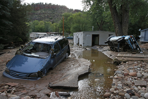 """FILE - In this Sept. 13, 2013 file photo, cars lay mired in mud deposited by floods in Lyons, Colo. Little more than a year after Colorado Gov. John Hickenlooper assured the world his wildfire-ravaged state was still """"open for business,"""" he may have to throw another lifeline to keep the state's billion-dollar tourism industry afloat.  (AP Photo/Brennan Linsley, File)"""
