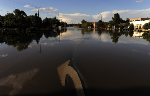 Floodwaters inundate a street in Loveland, Colo., on Monday, Sept. 16, 2013. Floodwaters have affected a 4,500 square-mile section of the state inundating entire neighborhoods and destroying bridges and roads. (AP Photo/Chris Schneider)