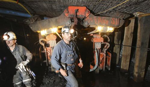 Rescuers walk past a Roof Bolter near the blocked tunnel in the Crandall Canyon Mine where six coal miners are trapped Wednesday, Aug. 8, 2007, northwest of Huntington, Utah. The collapse is located just over three miles from the surface. (AP Photo/Pool/Rick Bowmer)