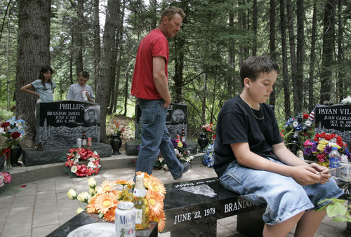 Jim Urquhart  |  The Salt Lake Tribune On Tuesday, Sterling Miller of Huntington, center, talks to his children Brooke Keser, 10, Mason Miller, 13, second from left, and Shane Keser 13, right, about the friends he lost in the Crandall Canyon Mine disaster Tuesday, August 4, 2009 at a memorial at the mine near Huntington. Thursday marks the two year anniversary of the disaster that ultimately claimed nine lives.