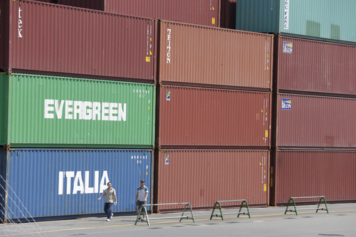 In this Aug. 19, 2013 photo, track drivers walk at a container terminal in Tokyo.  Japan's trade deficit swelled to a larger-than-forecast 960.3 billion yen ($9.8 billion) in August, as imports outpaced the growth in exports. (AP Photo/Shizuo Kambayashi)