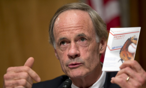 Committee Chairman Sen. Thomas Carper, D-Del., holds up a Priority Mail flyer during the Senate Homeland Security and Governmental Affairs Committee hearing on Capitol Hill, Thursday, Sept. 19, 2013, in Washington. According to Postmaster General Patrick Donahoe, the Postal Service may need an emergency rate increase to stay afloat. (AP Photo/Carolyn Kaster)