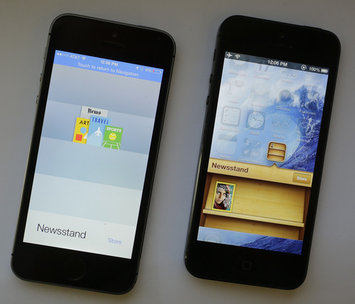 An iPhone with iOS 7 software, left, is displayed next to an iPhone with the older iOS 6 operating system, Tuesday, Sept. 17, 2013 in New York. Much of the new iOS 7 software is about cosmetic changes. The three-dimensional magazine rack in the Newsstand app is gone, for instance. (AP Photo/Mark Lennihan)
