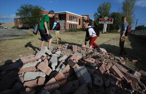 Francisco Kjolseth  |  The Salt Lake Tribune Granger High students pick through bricks of their old school put aside for souvenirs as crews begin the tear down process on Wednesday, Sept. 18, 2013, in West Valley