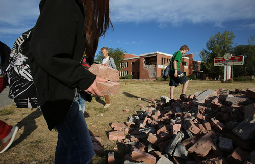Francisco Kjolseth  |  The Salt Lake Tribune Students pick through bricks set aside for souvenirs as the old Granger High school in West Valley City begins to come down with crews starting the demolition process on Wednesday, Sept. 18, 2013.