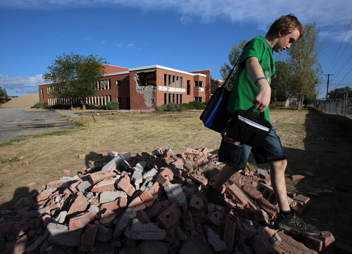 Francisco Kjolseth  |  The Salt Lake Tribune Budd Braithwaite, 14, a freshman, walks on some of the bricks put aside for students as the old Granger High school in West Valley City begins to come down on Wednesday, Sept. 18, 2013.