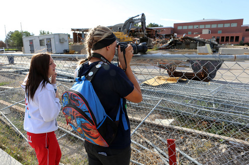 "Francisco Kjolseth  |  The Salt Lake Tribune Granger High seniors Summer Judd, left, and Kelsie Morandy, both 17, of the school yearbook staff, take pictures of the teardown process of their old school in West Valley City. ""It's a little depressing,"" said Morandy as they walked around the school on Wednesday, Sept. 18, 2013, for the start of the teardown process."