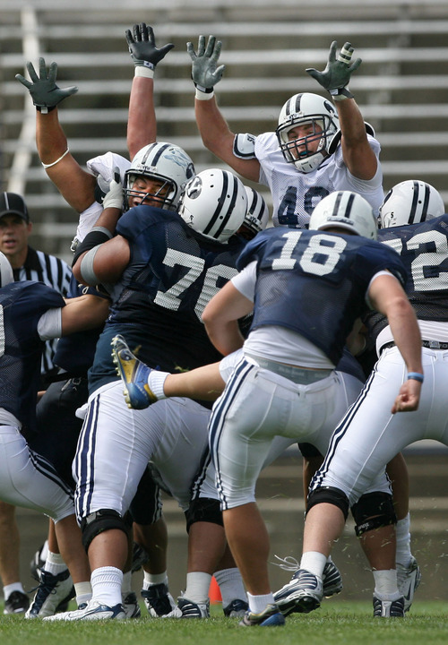 At right, linebacker Jadon Wagner goes up with his defensive teammates to try to block a field goal attempt by freshman kicker Justin Sorensen during scrimmage. BYU holds its first football scrimmage preparing for  the 2008 season Saturday, August 9, 2008, at Lavell Edwards Stadium. Salt Lake Tribune / Scott Sommerdorf
