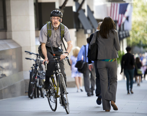 """Retired physician David Hilfiker, of Washington, leaves the National Press Club on his bike after talking about his life with Aalzheimer's in Washington, Thursday, Sept. 19, 2013. Hilfiker, was diagnosed in September 2012, and has been writing about the experience of losing his mental capacity in his blog """"Watching the Lights Go Out."""" Nearly half of all seniors who need some form of long-term care, from help at home to full-time care in a facility, have dementia, the World Alzheimer Report said Thursday. (AP Photo/Cliff Owen)"""
