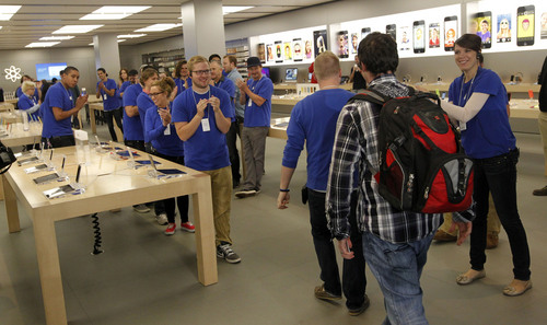 Al Hartmann  |  The Salt Lake Tribune Apple Store employees greet one of the first customers in line at City Creek Center's Apple Store early Friday morning September 20 to be among the first to purchase the new iPhone 5S.