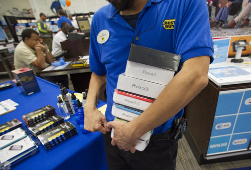 A manager brings out a stack of new iPhone 5s and iPhone 5c phones  on the day of their release at a Best Buy in Atlanta, Friday, Sept. 20, 2013. (AP Photo/John Amis)