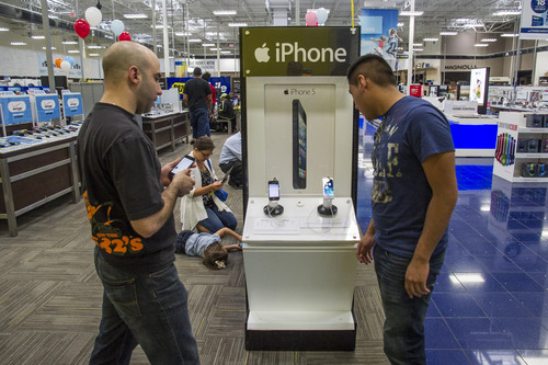 Alex Guglielimo, left, and Joel Escobar check out the new iPhone 5s on display at a Best Buy in Atlanta, Friday, Sept. 20, 2013. Friday is the first time Apple is releasing two different iPhone models at once. (AP Photo/John Amis)