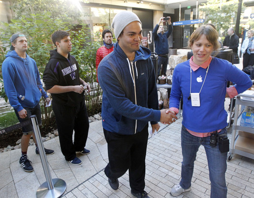 Al Hartmann  |  The Salt Lake Tribune Apple Store employee, right, greets one of the first customers in line at City Creek Center's Apple Store early Friday morning September 20 to be among the first to purchase the new iPhone 5S.