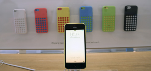 A row of iPhone 5c phones are on display at the Apple Store on Lincoln Road in Miami Beach, Fla., Friday, Sept. 20, 2013, the first day of sales for the phone. (AP Photo/J Pat Carter)