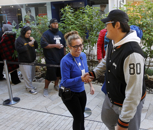 Al Hartmann  |  The Salt Lake Tribune Apple Store employee, left, greets one of the first customers in line at City Creek Center's Apple Store early Friday morning September 20 to be among the first to purchase the new iPhone 5S.