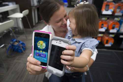 Isabel Ramo, 3, right, compares her iPhone 4 with her mom Christen Ramo's new  iPhone 5s  for a photographer on the day of the release, at a Best Buy in Atlanta, Friday, Sept. 20, 2013. (AP Photo/John Amis)