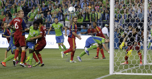 Real Salt Lake's Kyle Beckerman, center, looks on as a header shot by Seattle Sounders' Zach Scott, center right, is deflected by Real Salt Lake goalkeeper Nick Rimando, right, in the first half of an MLS soccer match, Friday, Sept. 13, 2013, in Seattle. (AP Photo/Ted S. Warren)