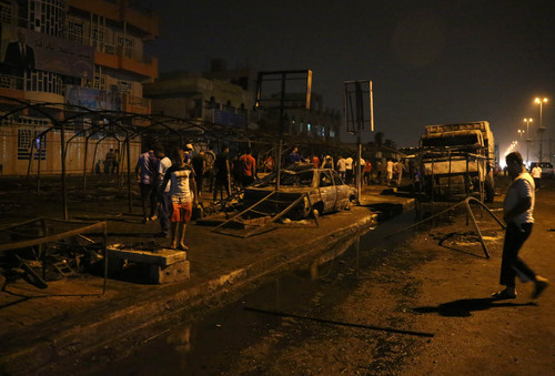 People inspect the site of a double suicide bomb attack,  in the Shiite neighborhood of Sadr city in Baghdad, Iraq, Saturday, Sept. 21, 2013. Two suicide bombers, one in an explosives-laden car and the other on foot, hit a cluster of funeral tents packed with mourning families in a Shiite neighborhood in Baghdad, the deadliest in a string of attacks around Iraq that killed at least 92 on Saturday. (AP Photo/Hadi Mizban)