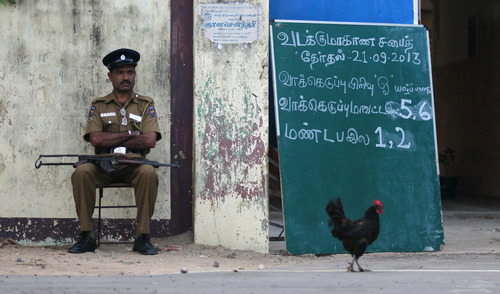 A Sri Lankan police officer guards outside a polling station before the beginning of voting in Jaffna, Sri Lanka, Saturday, Sept. 21, 2013. The elections are seen by the United Nations and the world community as a crucial test of reconciliation between the Tamils and majority ethnic Sinhalese, who control the government and the military. (AP Photo/Eranga Jayawardena)