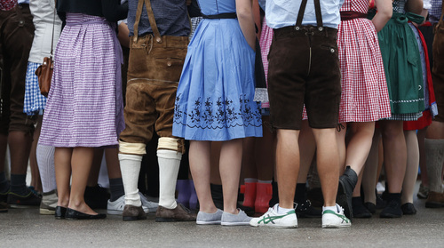 """People await the opening of the Bavarian """"Oktoberfest"""" beer festival in Munich, southern Germany, Saturday, Sept. 21, 2013. The world's largest beer festival, to be held from Sept. 21 to Oct. 6, 2013, is expected to attract more than six million guests from around the world. (AP Photo/Matthias Schrader)"""