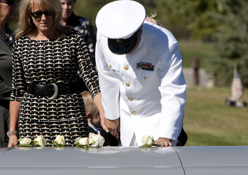 Steve Griffin  |  The Salt Lake Tribune  With his wife, Susie holding his hand, Naval Reservist, Steve Carlson, places his hand on the casket of his son, Iraq war veteran James Steven Carlson, during graveside services at the Utah Veteran's Memorial Park in Bluffdale, Utah Friday, Sept. 20, 2013.