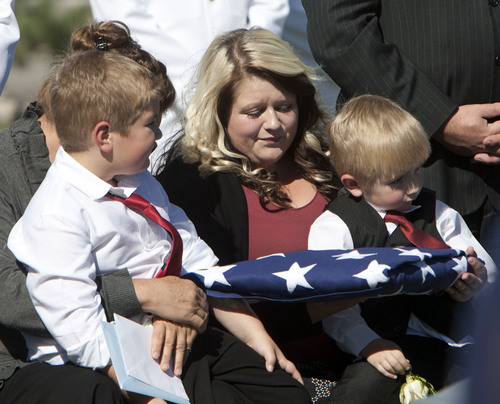 Steve Griffin  |  The Salt Lake Tribune  Kristen Carlson and her sons Jonathan, 6, and Ethan, 3, holds the American Flag that covered the casket of their husband and father, Iraq war veteran James Steven Carlson, during graveside services at the Utah Veteran's Memorial Park in Bluffdale, Utah Friday, Sept. 20, 2013.