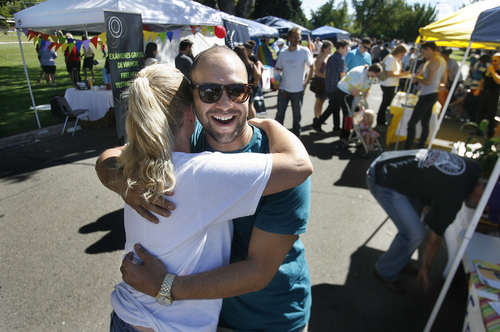 """Scott Sommerdorf      The Salt Lake Tribune Corey Howard of Mormons Building Bridges gives Michel Knowles a hug at her """"Free Hugs"""" stand at Provo's first Pride Festival, held at Memorial Park in Provo on Saturday."""