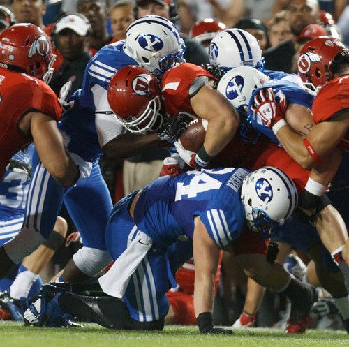 Trent Nelson  |  The Salt Lake Tribune Utah Utes tight end Jake Murphy (82) is brought down by BYU defenders in the first quarter as the BYU Cougars host the Utah Utes, college football Saturday, September 21, 2013 at LaVell Edwards Stadium in Provo.